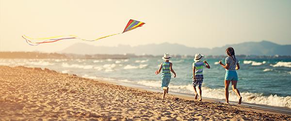 Kids chasing kite on beach