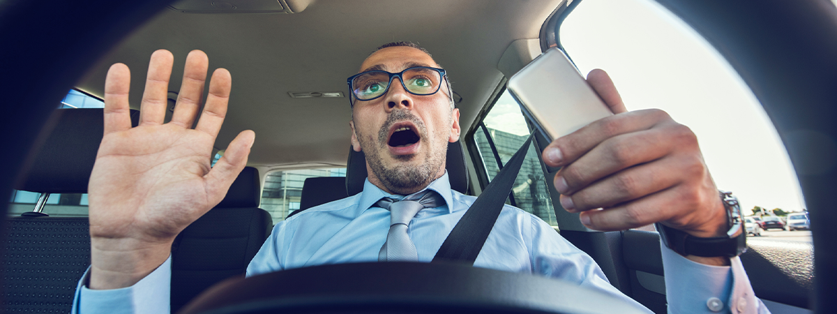Distracted driver with phone in his hands