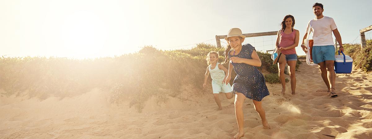 Family running onto beach