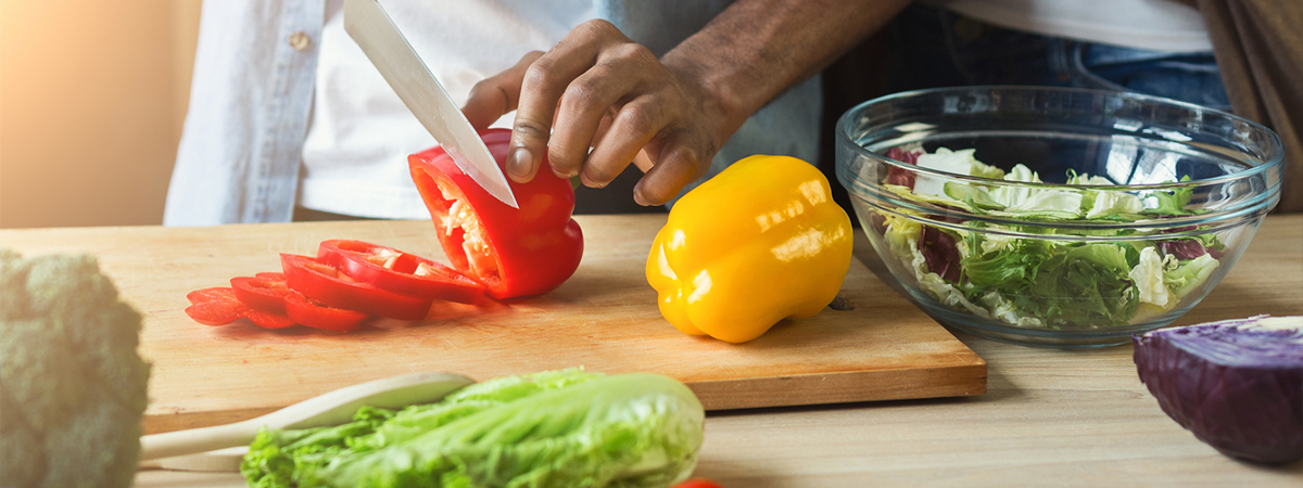 Man cutting red and yellow peppers on wooden cutting board.