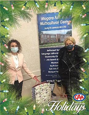An organizer from the Niagara Folk Arts Multicultural Centre and Mahasti Khoshnoud hold mask donations.