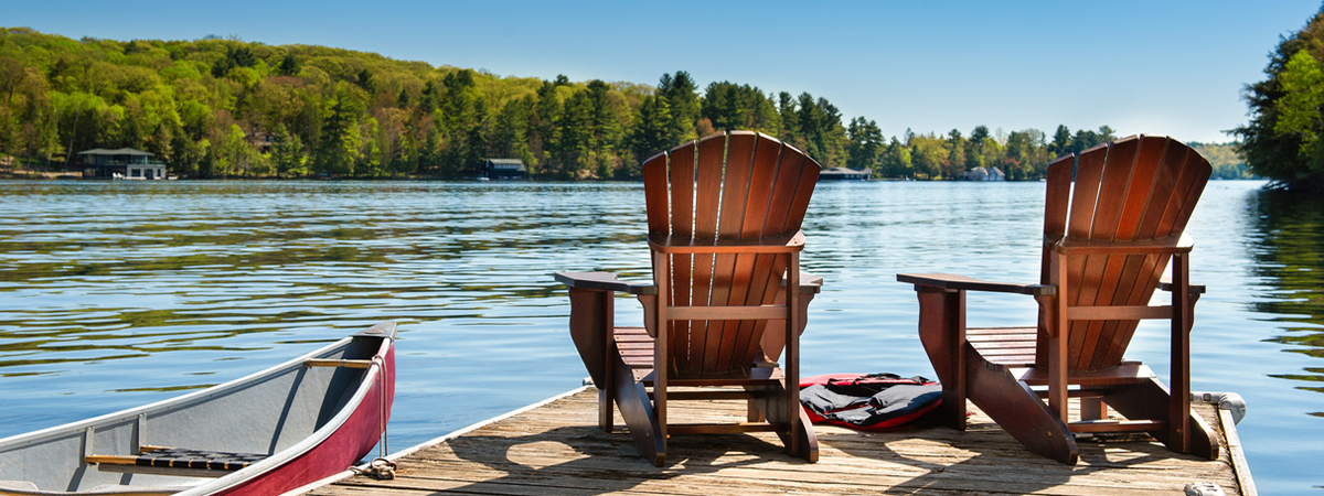Muskoka chairs on a dock beside a canoe looking out to a lake