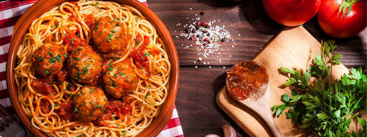 A plate of spaghetti and meatballs surrounded by cooking tools and ingredients