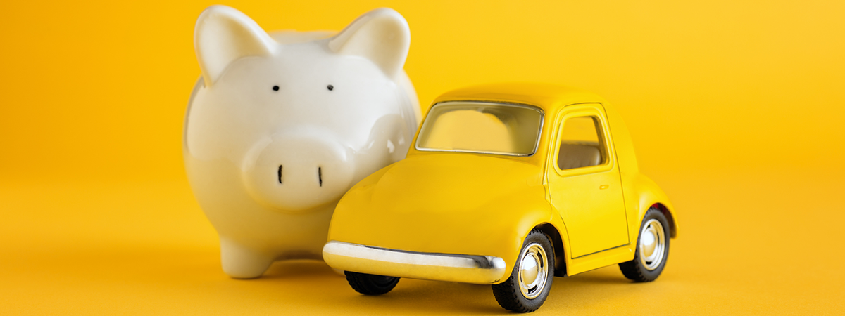White piggy bank, yellow toy car on yellow background.