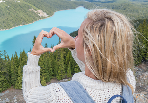 Woman making a heart with her hands on top of a hill overlooking wilderness