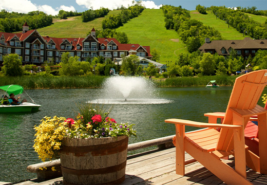 Adirondack chairs overlooking the nearby pond in the Blue Mountain Village