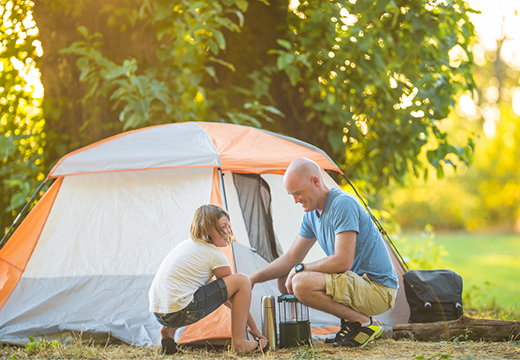 Dad and daughter putting tent together on a camping trip