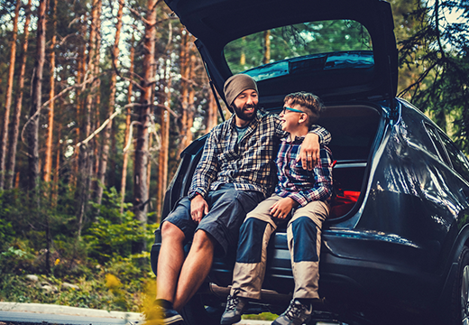 Father and son travelling by car in the forest.