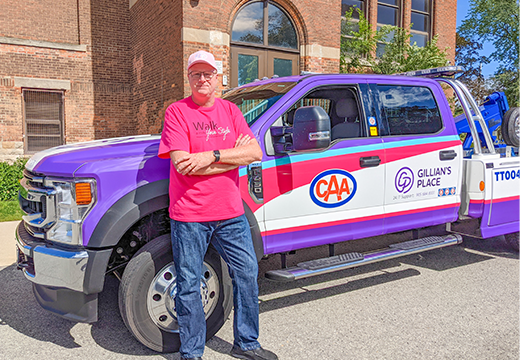 CAA President and CEO, Peter Van Hezewyk, stands beside road service with Gillian's Place branding in support of Walk a Mile - Your Style event.