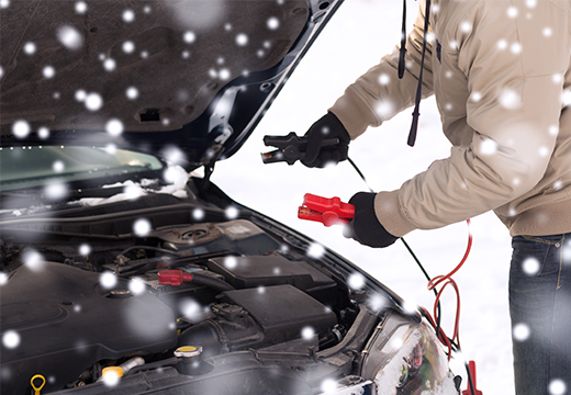 Driver using jumper cables to start dead battery in middle of winter.