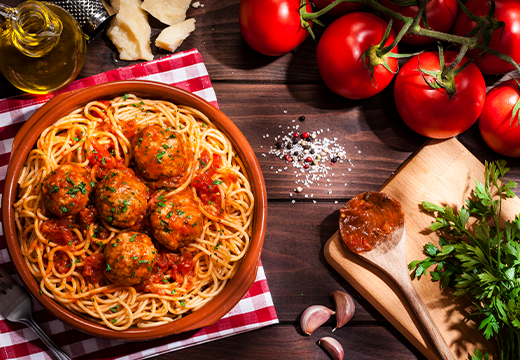 Plate of spaghetti and meatballs surrounded by cooking utensils and ingredients